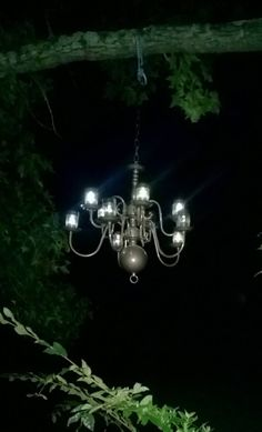I bought this chandelier for $5, removed the wiring and glued solar lights in the sockets. Now it hangs from a limb down by the pond and we just love it!