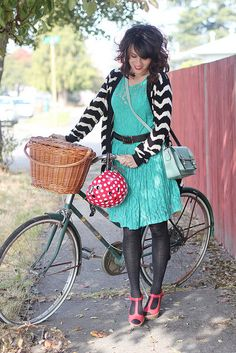 black and white chevron striped cardigan over bright blue dress and black belt. the red shoes and black tights MAKE the outfit. this is how i LOVE to dress, she jus happens to do it better..probably cuz she's taller. people with long legs always pull stuff off better. damn them. cute bicycle basket.