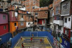 gasoline-station: Surrounded Football People take part in a football match held at the Tavares Bastos slum in Rio de Janeiro. The World Cup will be held in 12 cities in Brazil from June 12 till July Picture: Pilar Olivares / Reuters Source: The Telegraph Street Football, Soccer Match, Football Match, Soccer Art, Football Field, Basketball, Cities, Spiegel Online, Building Exterior