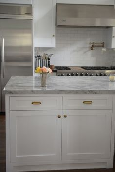 Kitchen - white veined countertops with silver and gold details. white background and cabinetry | Cupcakes & Cashmere