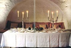 John Stefanidis: Patmos, Greece: Silver candlesticks stand on a simple trestle table covered by a linen cloth with sharp folds reminiscent of medieval paintings [Rooms 1988].