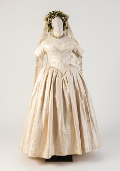 OBJECT 37 - White woven silk wedding dress, with embroidered net lace veil, 1840s. Fashion Museum Bath.