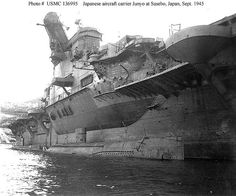 """Another view of the carrier Junyo, in Sasebo in 1945 after the cessation of hostilities. There are two small coastal submarines moored alongside, one right under the massive sponson supporting the island. The hull had to have a considerable bulge on the opposite side to compensate for the weight of the sponson and island structure.  The two ships of this class, Junyo and Hiyo were designed ostensibly as 27500 grt passenger liners, but a year before launching they were """"taken over"""" by the…"""