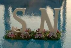 Floating monogram letters and flowers pool decoration for outdoor weddings
