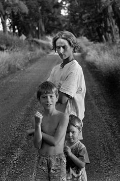 Larry Towell CANADA. Lambton County, Ontario. 1997. Moses (back), Noah (centre), and Isaac (bottom) TOWELL stand on the road that runs in front of their home in rural Ontario.
