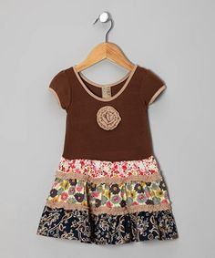 This girly frock's comfy cotton top gives way to a lively tiered skirt, while an intricately crafted fabric rosette and contrast piping add unique charm.