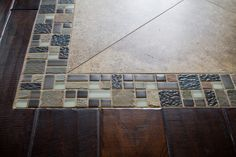 CLOSE-UP: Love this custom tile inset on the dark hardwood floors in the entryway. Great alternative to a rug! http://flahertysflooring.com