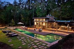 A large covered patio with a bar and dining area sits aside this stunning poolhouse. On the spacious lawn, geometric pavers turn the grass into an artistic statement.