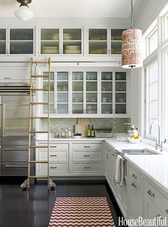 Glass Front Clear glass fronts can showcase an impressive dinnerware collection, like in this subtle kitchen designed by Katie Ridder. Better yet, a rolling ladder lets the resident chef peruse the stash with ease.