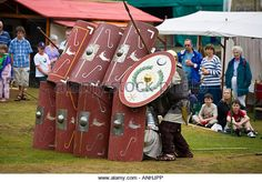 Roman soldiers in defensive formation with shields and weaponry at a Roman army reenactment, Chedworth Villa, Gloucestershire - Stock Image
