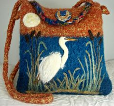 This beautiful bag is knitted out of 100% baby alpaca yarn, then felted and needle felted. Alpaca purses are luxurious and soft feeling but yet study. This beautiful Egret stands in its habitat in the slowly setting sun. The bag has an inside pocket and closes with an amazingly beautiful designer ceramic button. The measurements are: 12 X 12 X 2. The ADJUSTABLE strap has a 23 drop but can easily be shortened. Gorgeous colors