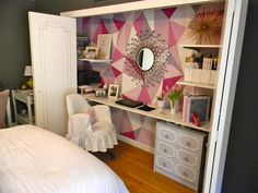 Fantastic office in closet with bi-fold doors painted with gold trim, pink geometric pattern hand painted accent wall, sunburst mirror, white floating desk, gray Dorothy Draper style chest, white floating desk and white slipcover chair.