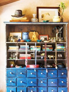 A vintage dresser stuffed with books, vintage finds, and meditation beads