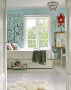 Väggarna i barnrummet är dekorerade med djur och växtlighet mot himmelsblå botten.