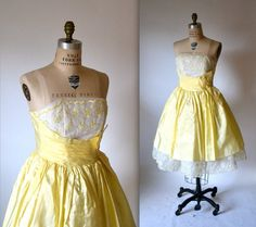 This Stunning Vintage prom dress party dress from the 50s features:    * Constructed in pale yellow taffeta with white embroidered organza at the