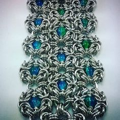 Athena's Wisdom Cuff done in silver aluminum with 6mm round blue and green crackle glass beads. These are available to custom order, in your choice of ring colors, and metals, as well as beads! $175