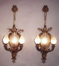 A Palatial Pair of French 19th/20th Century Louis XV Style Figural Gilt-Bronze and Frosted Molded-Glass Two-Light Wall Light Luminéres, each centered with an ovoid frosted glass plaque with a sun-burst below six frosted glass sun-rays protruding from above all ribbon-tied being held by a lion mask. The two cornucopias candle arms with frosted glass shades in the form of flames. Circa: Paris, 1890