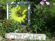 Old Window with a sunflower I painted on it and THE GARDEN sign I also handpainted
