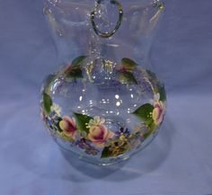 This heavy glass pitcher has been hand painted with a beautiful flower vine of berry pink colored roses, blue hydrangeas ranging in color from