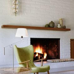 Off Center Fireplace Design Idea - Painted brick with long wood mantle piece.