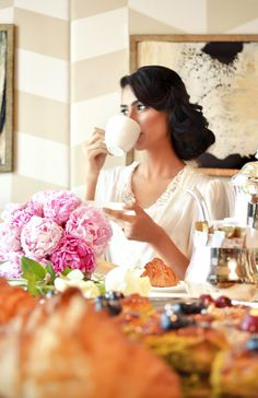 The bride takes a sip of her morning coffee, smiling to herself in anticipation of her wedding at The Ritz-Carlton, Dubai International Financial Centre.
