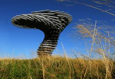 SINGING RINGING TREE  HILL-TOP MUSICAL SCULPTURE, 2004. A musical sculpture standing in the wind on a hill overlooking Burnley. From far and wide, the tree's profile is visible on the horizon.  Constructed of stacked pipes of varying lengths, orientated to lean into the directions of the prevailing wind. As the wind passes through the different lengths of pipe, it plays different chords. Each time you sit under the tree, looking out through the wind, you will hear a different song.