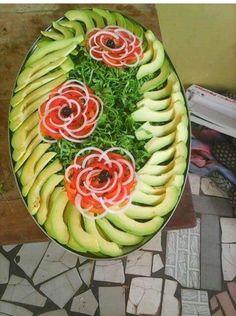 Cold entrée. Avocado lettuce tomatoes and onion. Cute salad presentation