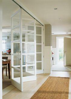 cloisons amovibles en verre et bois de couleur blanc, sol en parquette clair, tapis en rotin
