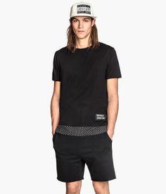 Knee-length shorts in sweatshirt fabric. Elasticized drawstring waistband, side pockets, one back pocket, and raw-edge hems.