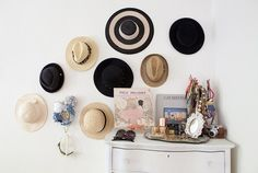 Need a way to store your hat so they don't lose their shape? Hang them on the wall like this; if you have alot of hats hang them up evenly spaced from each other in an interesting way or if you don't, arrange them around photos and a wall clock.