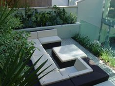 contemporary all weather rattan wicker woven lounge furniture with raised white rendered planter walls and water feature  QUESTION: can anyone suggest what range of modular furniture this is please? or similar UK available?