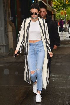 1 April Kendall Jenner was spotted out and about in NYC wearing a long, striped duster coat with ripped jeans.   - HarpersBAZAAR.co.uk