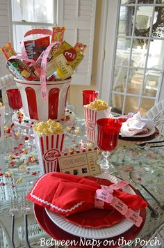 A string of ticket stubs work well as napkin rings.  They are loosely tied around the napkins. With scattered popcorn & stars for fun.