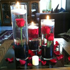Red roses with white floating candles and black rocks at the bottom. Super cute centerpieces.