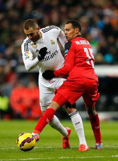 Karim Benzema of Real Madrid competes for the ball against Timothée Kolodziejczak of Sevilla during the La Liga match between Real Madrid CF and Sevilla FC at Estadio Santiago Bernabéu on February 4, 2015 in Madrid, Spain.