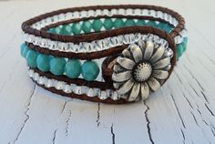 Czech glass turquoise colored beads, are hand stitched onto brown distressed leather. Tiny silver/crystal colored glass beads frame the turquoise. Finished with a pewter daisy button.  Measures 7 inches, and 3/4 wide  **Want to add a hand stamped letter charm? Click here! https://www.etsy.com/shop/thehummingbead?section_id=12843953    **Click here to see more of my designs: http://www.thehummingbead.etsy.com    **Need this is a different size? Click the blue contact button on your right to…