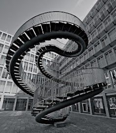 """This steel staircase sculpture titled """"Umschreibung"""" is a wonderful piece of art designed by Olafur Eliasson. This beautiful merging of art and architecture is a 9 meter-high walk-double spiral of steel in the entrance of the KPMG ( a global accounting firm ) office building in Munich, Germany."""