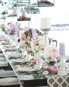 Pillar candles and glass lanterns illuminate a glorious abundance of centerpieces.  #touchofwhimsy #letsgetwhimsical #weddings #weddingplanner #weddingcoordinator #eventplanner #eventcoordinator #weddingtrends #weddingdecor #weddingvenue #weddingdesign