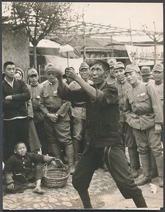 Japanese Army soldiers watch a Chinese street performer in Nanking, China, 1938