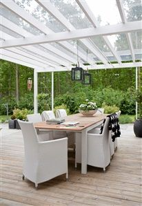 gorgeous covered decking in pale wood with white outdoor rattan dining chairs and black pots = husohem Uteplats