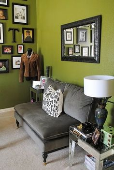 little grey couch, olive green walls, and wall of frames.