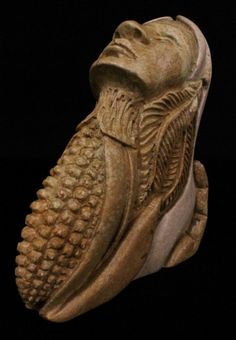 Stone Carving Of A Hand Holding A Woman With Eagle Feathers And Corn. | Kitigan.com #Art #StoneCarving
