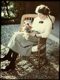 Jonge vrouw (gekleed in een witte blouse en een grijze rok en met vlechten in het haar) zittend in een stoel op grint, met een bosje bloemen in haar handen, anoniem, 1907 - 1930