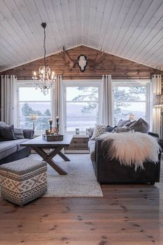 a cozy cabin style living room with a wooden wall and several windows that bring views in