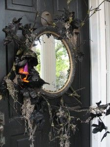 INSPIRATION: made up of black dead sticks and faux flowers secured to the back of a large round mirror; the look is finished off with Spanish moss and a crow wearing a witch's hat