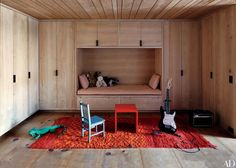 Simrel Achenbach of Descience Laboratories, in collaboration with designer Daniel Sachs of Sachs Lindores, combined adjacent lofts to create a Manhattan residence for photographers Inez van Lamsweerde, Vinoodh Matadin, and their son, Charles. In the playroom, bleached-alder-wood closets provide a neutral contrast to the richly colored Moroccan carpet.