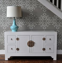 painted asian cabinet, stenciled wall, pop of color with turquoise lamp...
