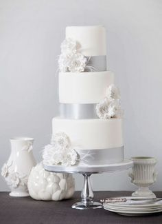 Bobbette & Belle Feathers & Flowers wedding cake. Feathers & Flowers         This three tier cake has extra high tiers to give     a towering impression, the ruffled sugar flowers are enhanced with sparkling silver sugar pearls and touches of fine ostrich feathers.
