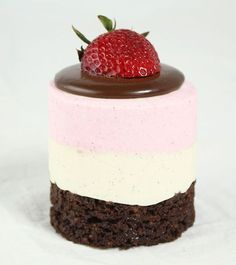 A close up photo of a Neapolitan Mousse Cake garnished with Dark Chocolate Ganache and fresh strawberry.