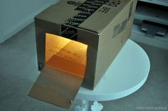 DIY overhead projector using a cardboard box to project and paint an image on a wall